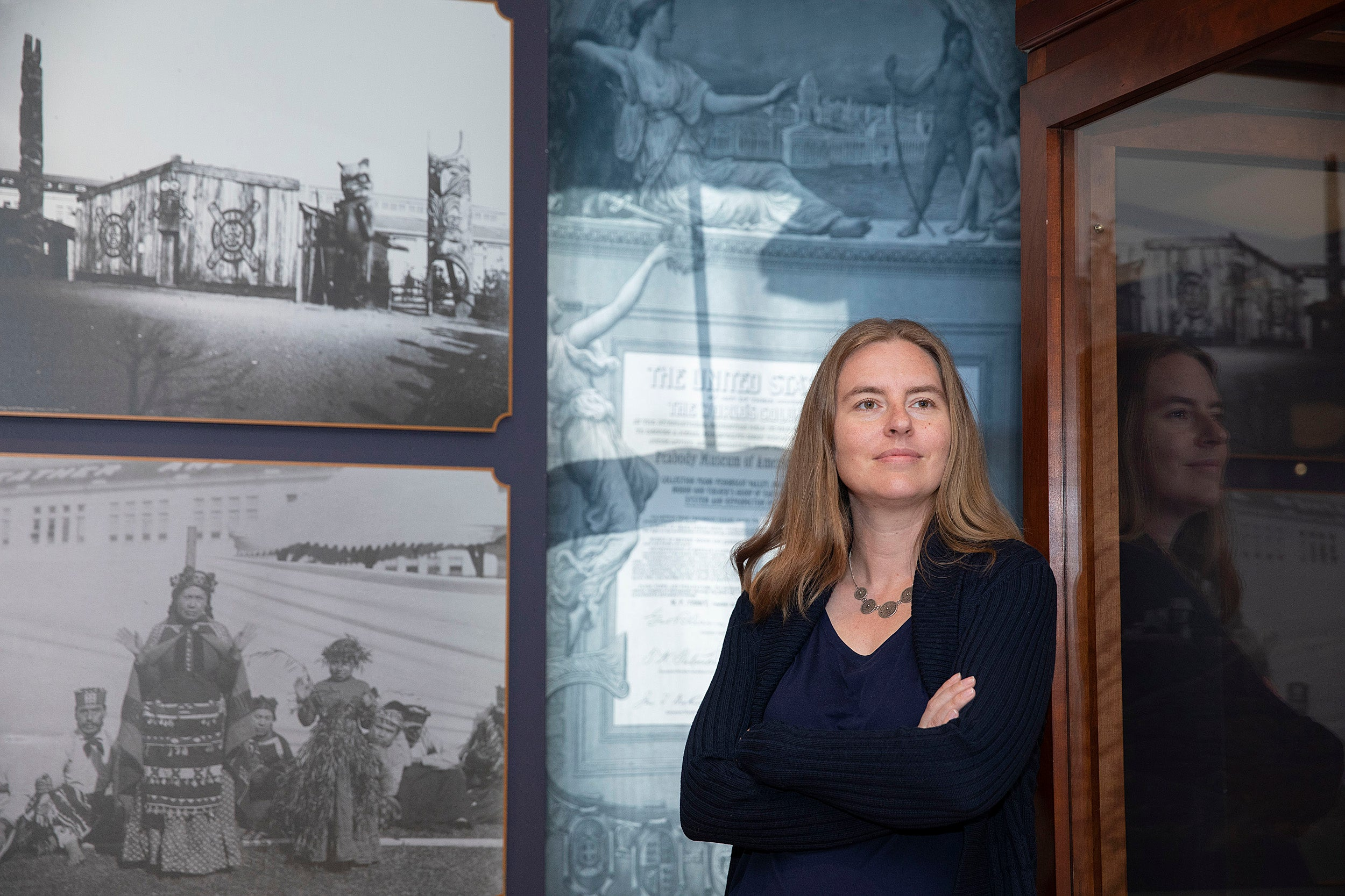 Christina Warinner is a new faculty member photographed in front of a display at the Peabody Museum.