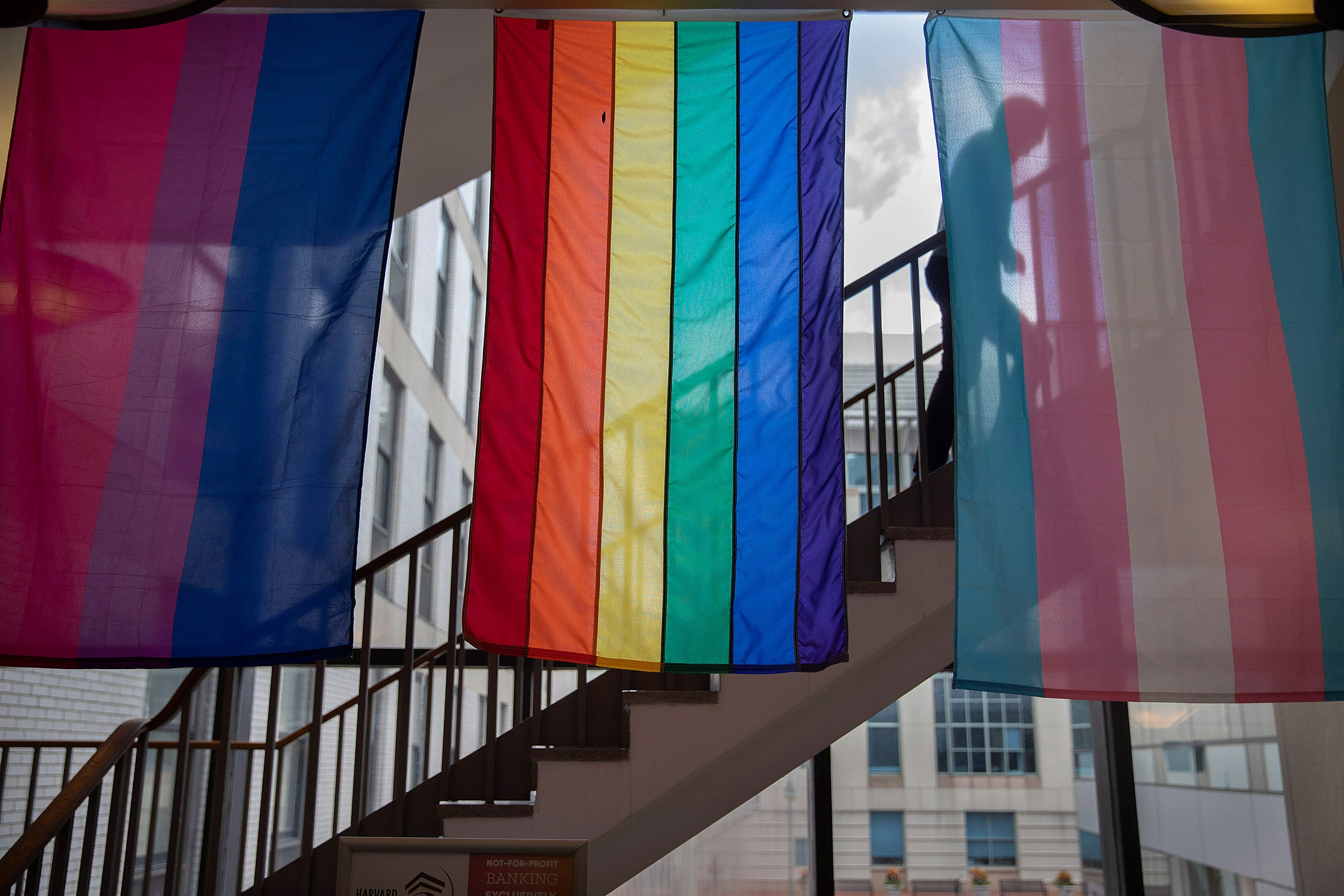 Student walking up stairway with colorful flags hanging from ceiling.