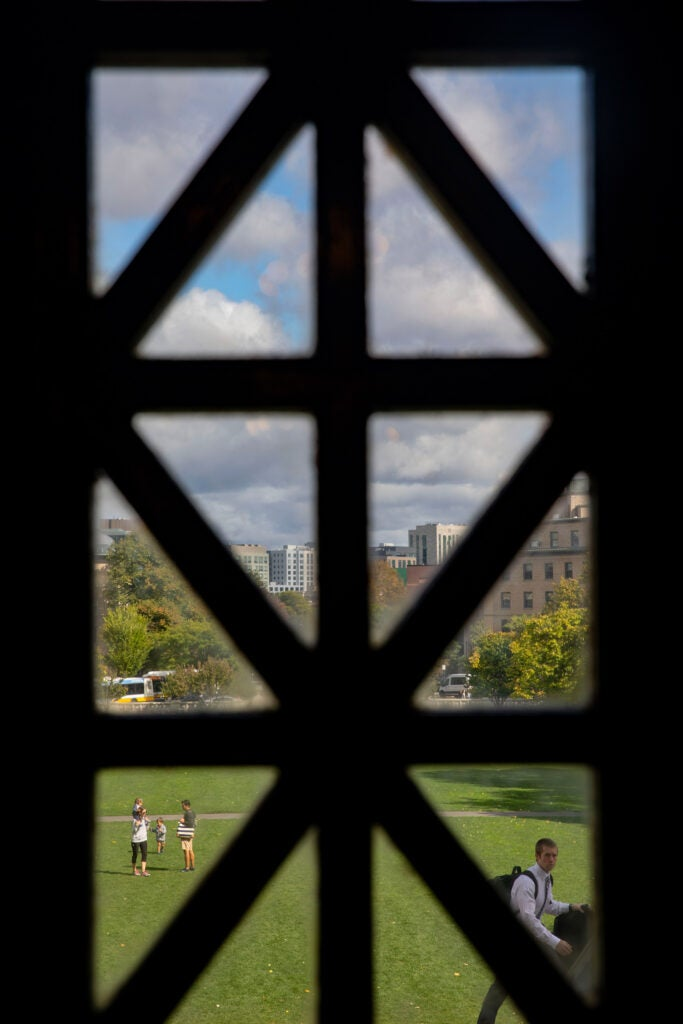 A dark window frames a family in the courtyard at Harvard Medical School.
