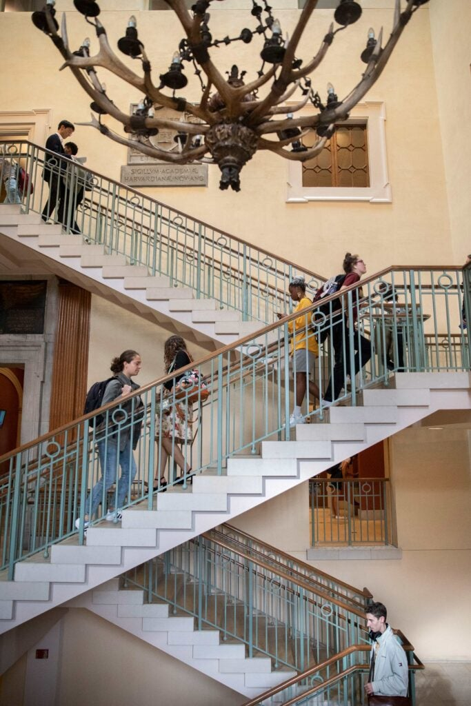 Students walking up and down a three level staircase under a decorative chandelier.