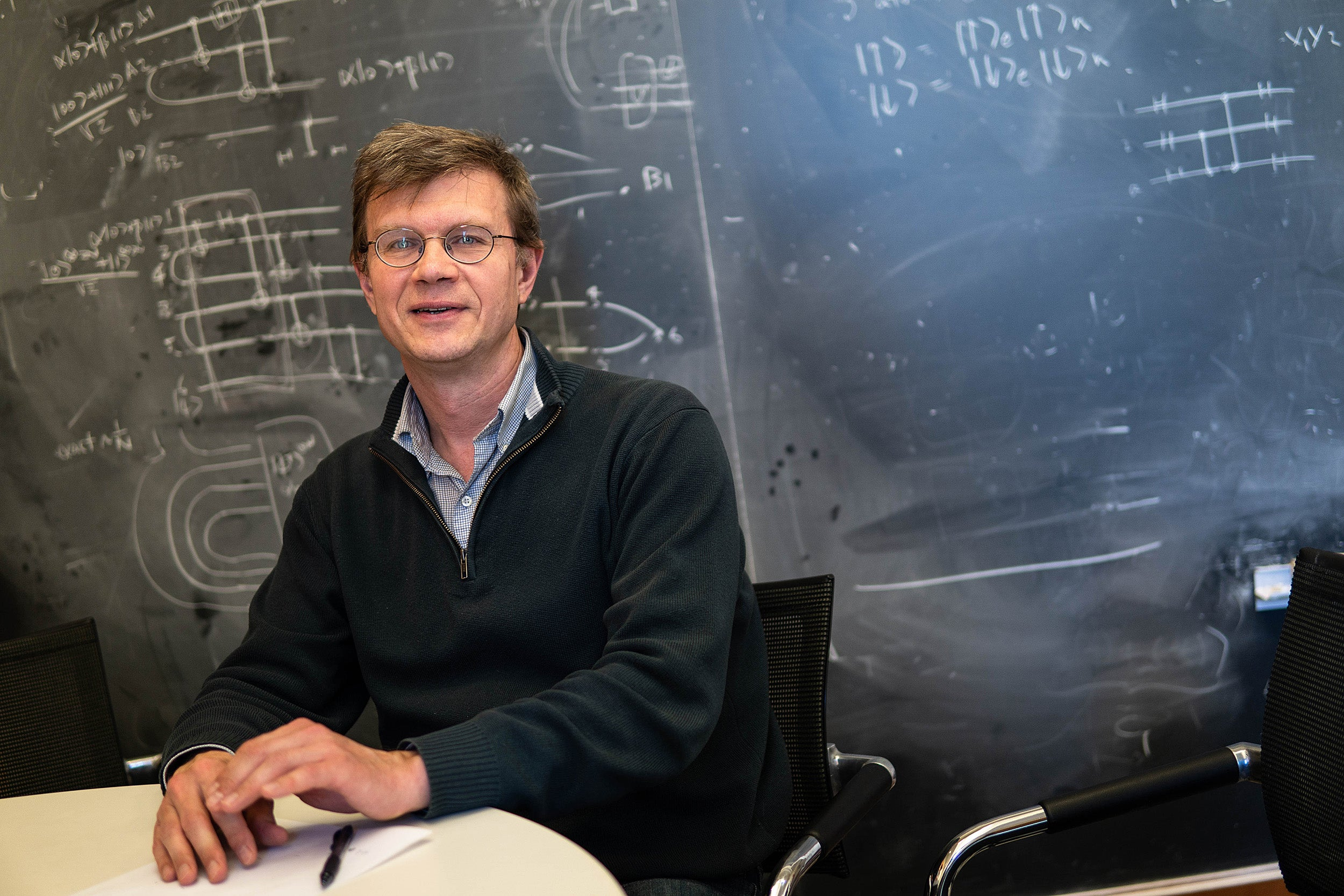Professor Mikhail Lukin, co-director of Harvard's Quantum Initiative, in his classroom with a blackboard filed with equations.