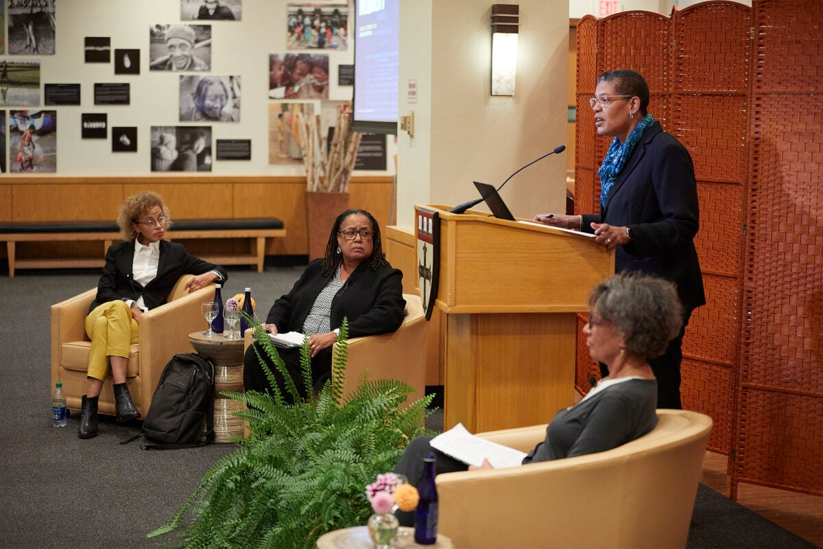 "Harvard Chan School Dean Michelle A. Williams (podium) addressed the audience at the ""400 Years of Inequality"" event. Linda Villarosa (from left), Evelynn M. Hammonds, and Mary Bassett shared in the discussion."