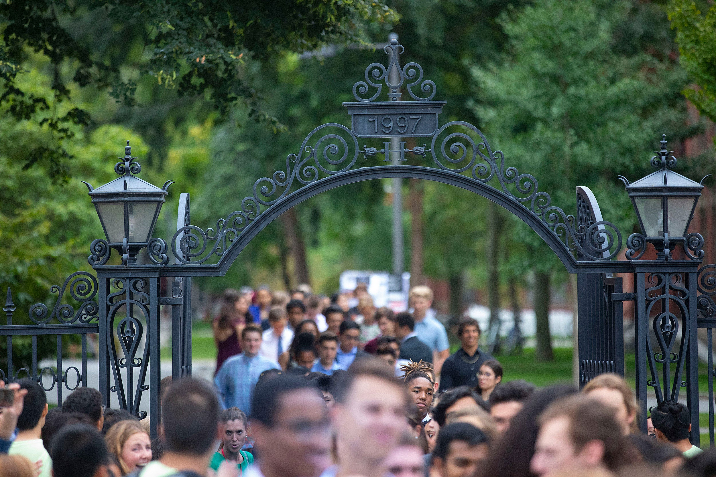 A large crowd of Harvard students walking through a Harvard gate.