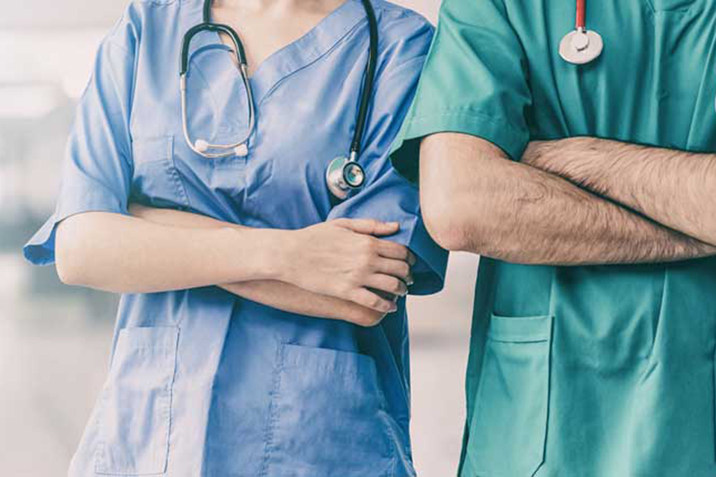 Two people standing next to each other in hospital scrubs with arms crossed