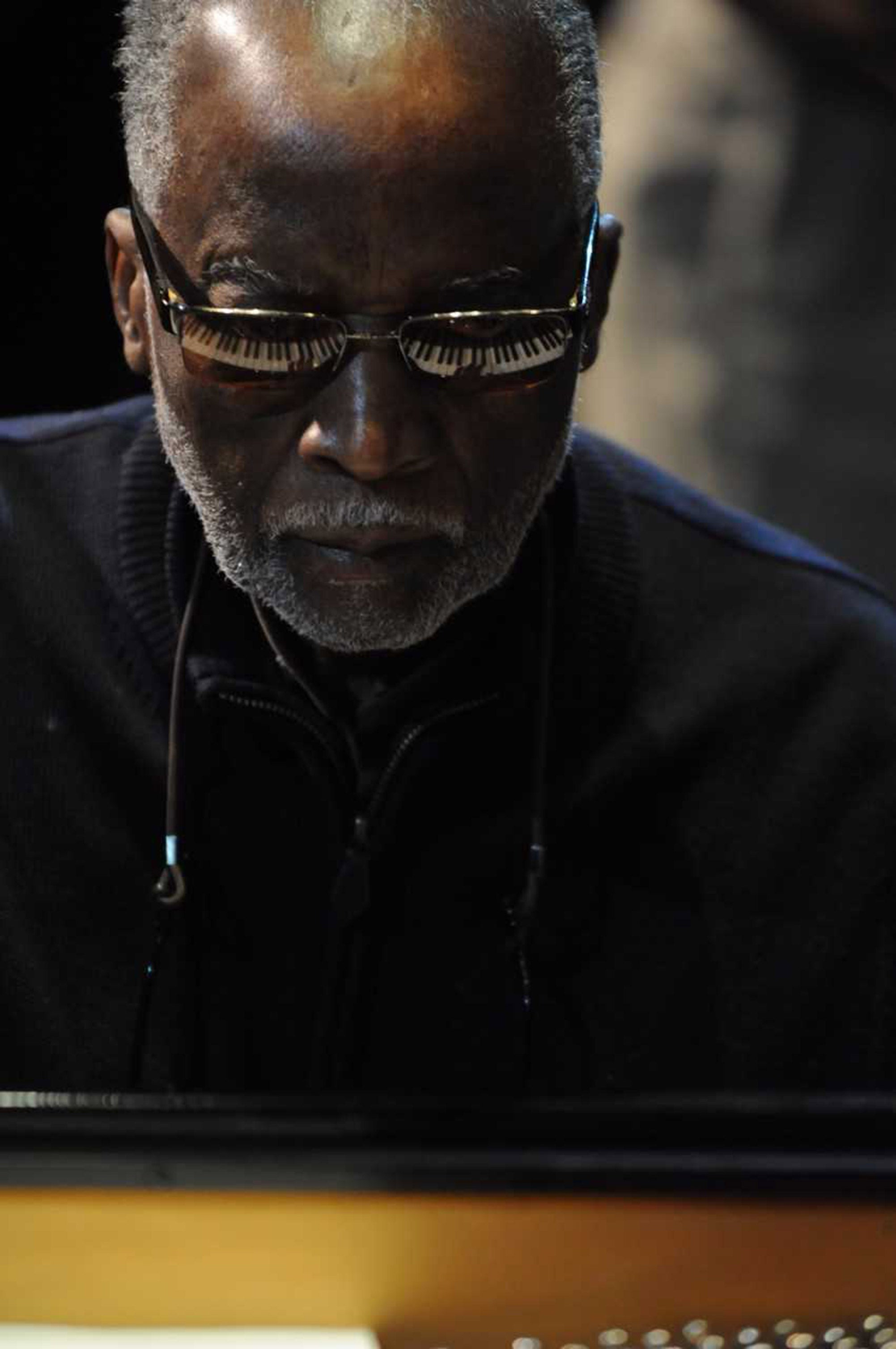 Ahmad Jamal, 2013 with piano keys reflected in glasses