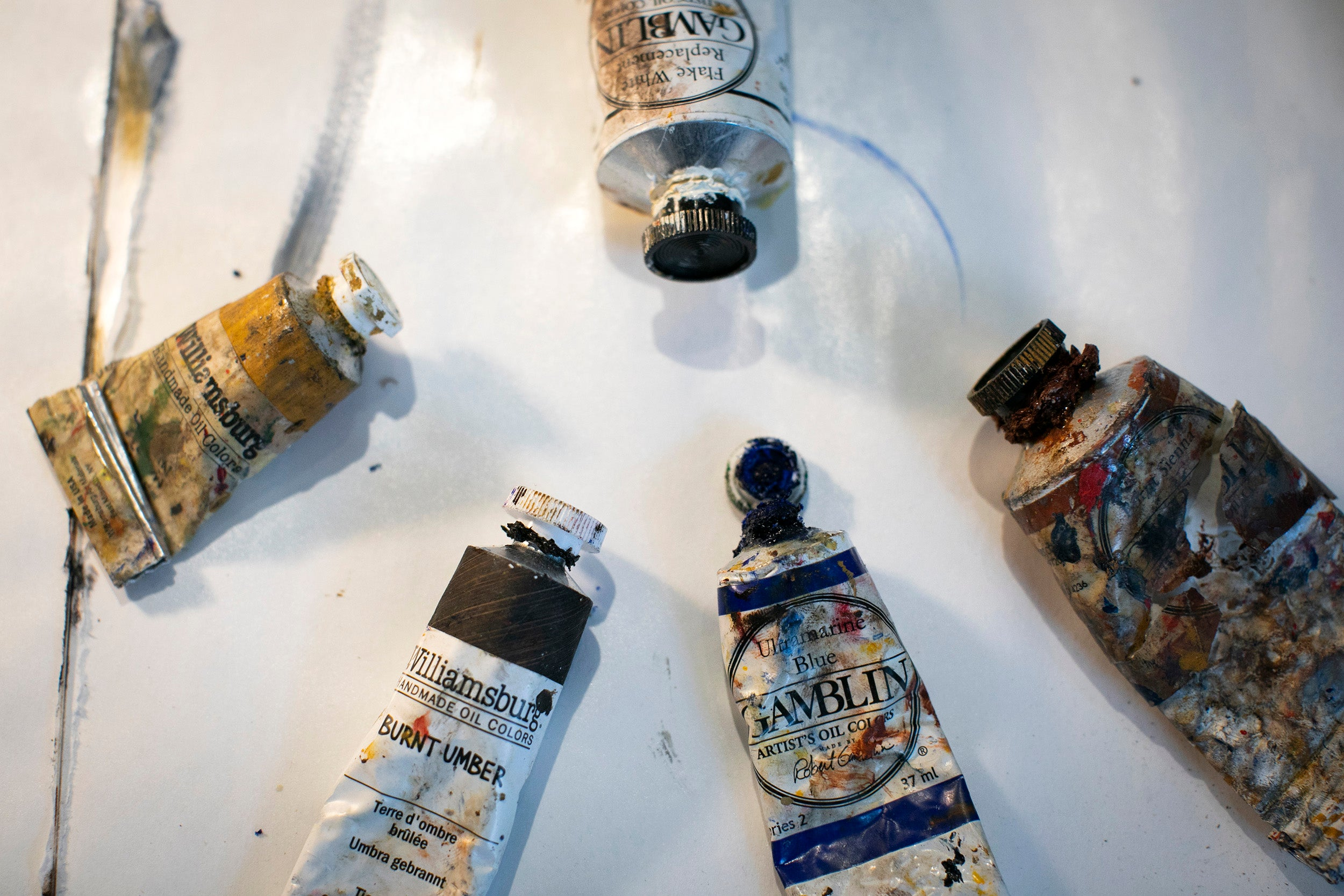 Five oil paint tubes lay on a table.