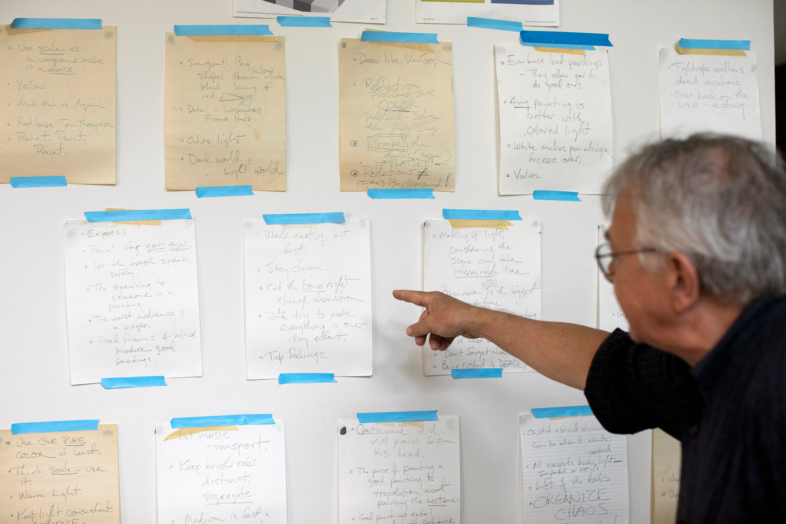 Stephen Coit points to an array of helpful and inspiration notes taped to his studio wall.