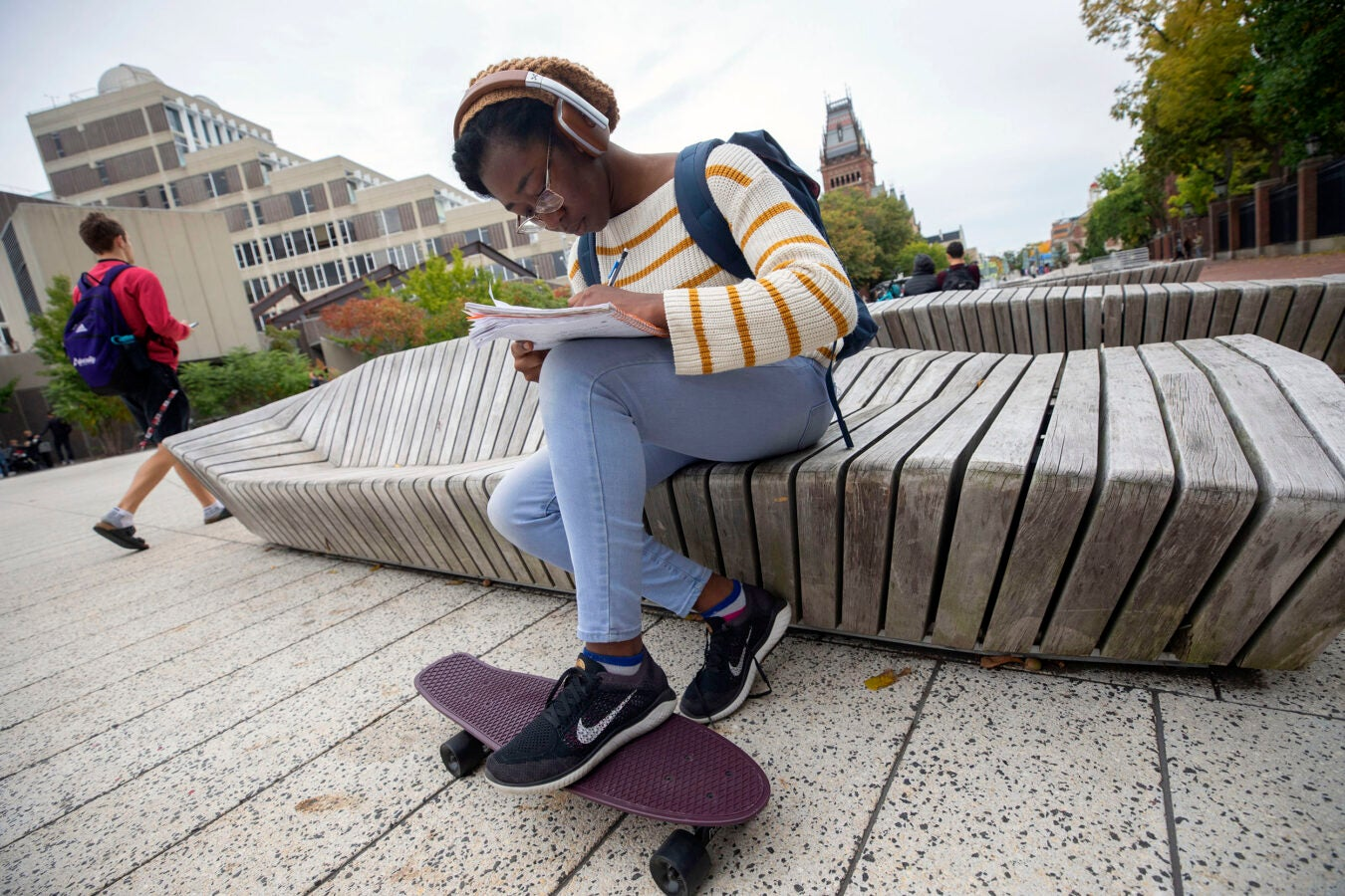 "Edith ""Tomi"" Siyanbade does homework at the Science Center Plaza, resting her foot on a skateboard that she uses for transportation."