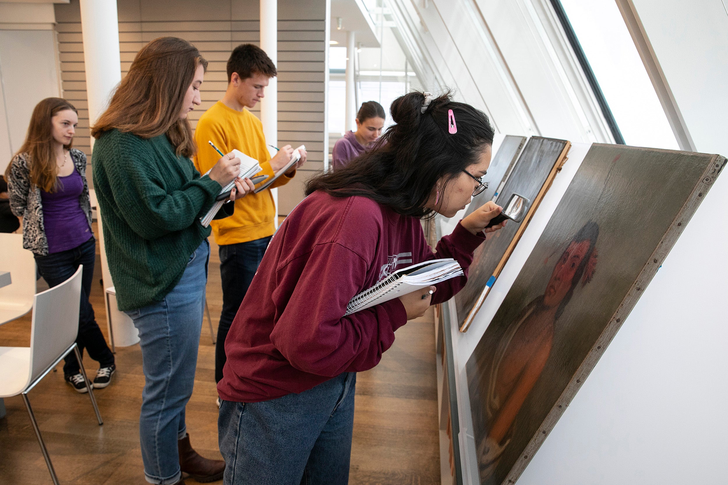 students study oil paintings with magnifying glasses