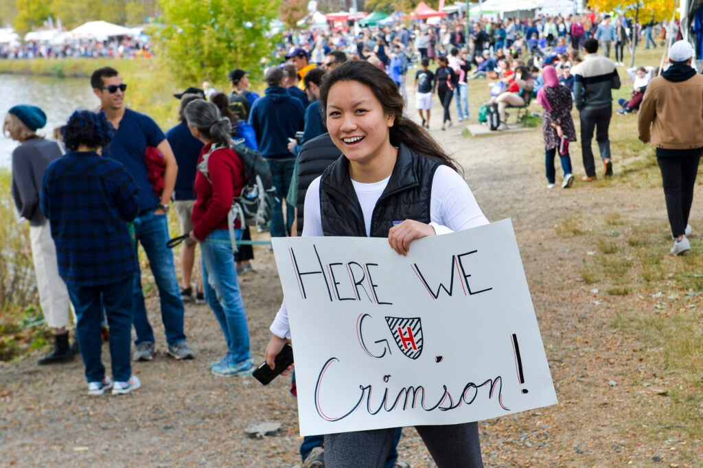 "Student Athena Ye holds a sign ""Here we go Crimson"" during Head of the Charles weekend."
