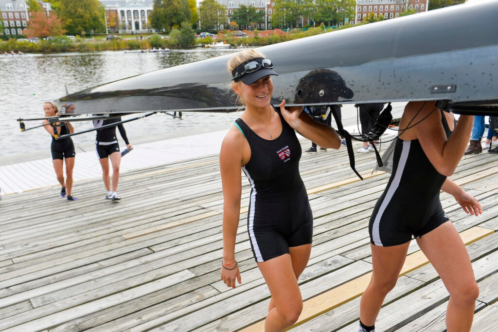 Molly Lesser '20, co-captain of the Radcliffe varsity lightweight team, and teammates including Analysia Watley '21, rear, hoist their boat into Weld Boathouse.