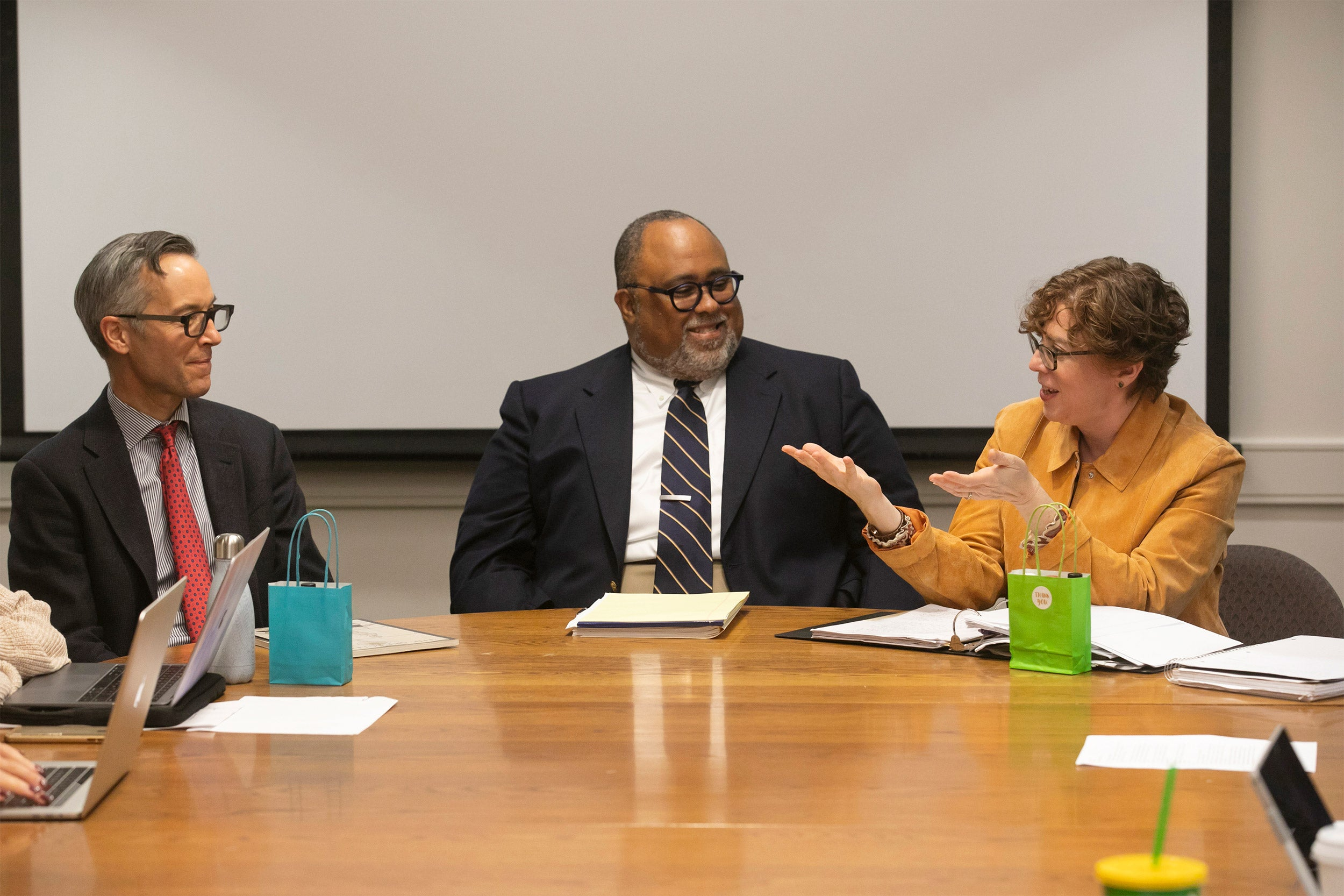 Professor Robin Bernstein speaking with Deans Robin Kelsey and Lawrence Bobo at a conference table.