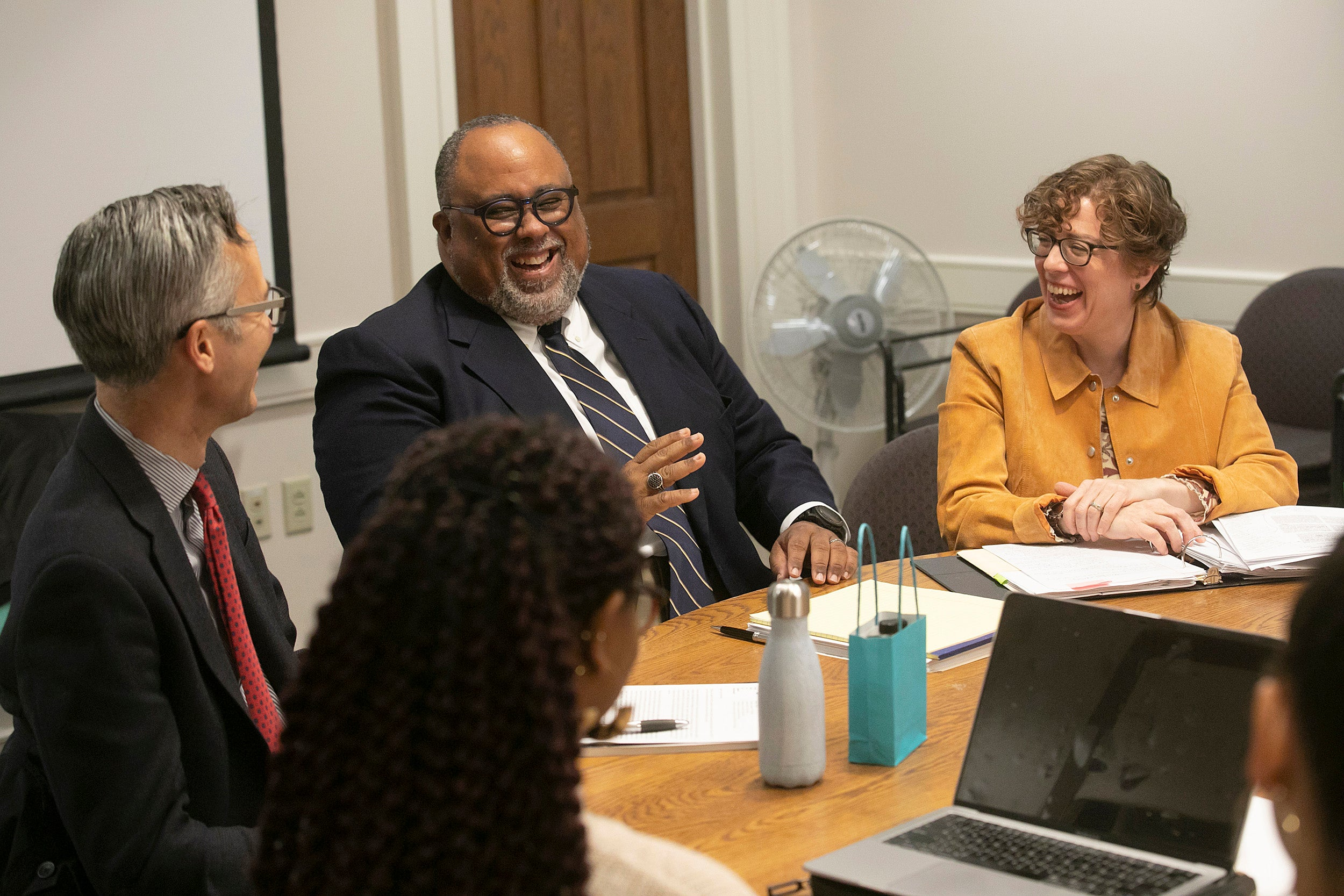 Four people laugh around a conference table.