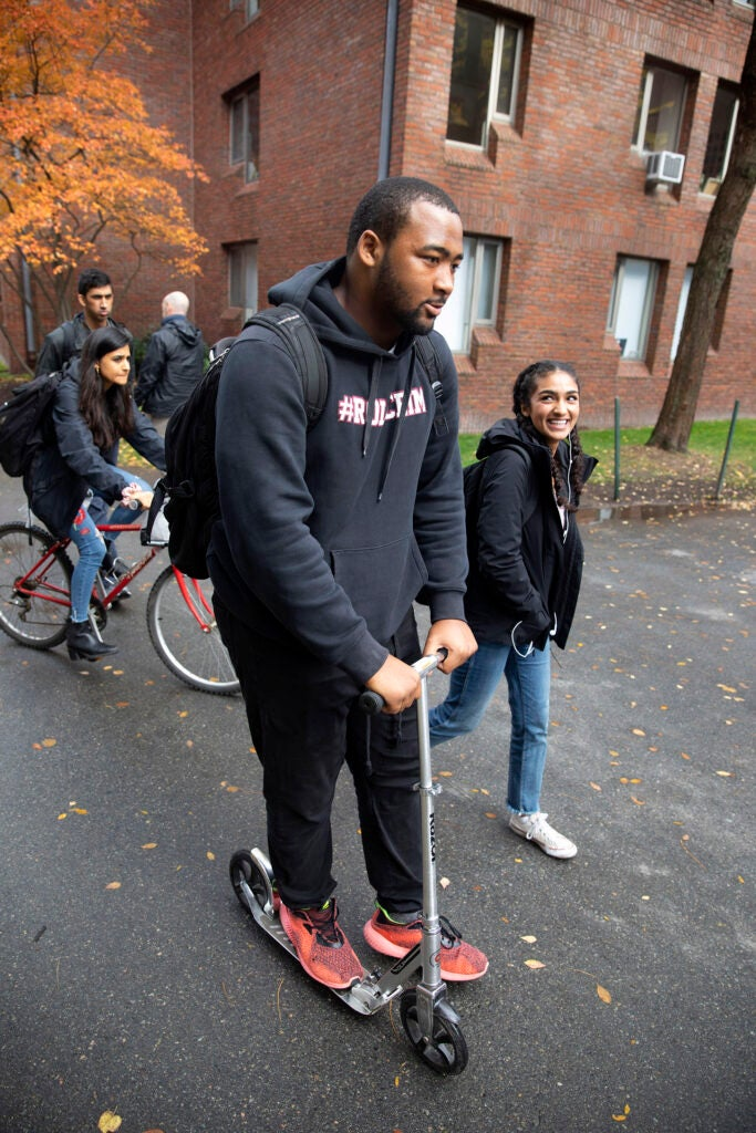 Jacob Sykes rides his scooter, and Noor Kamal walks across campus.