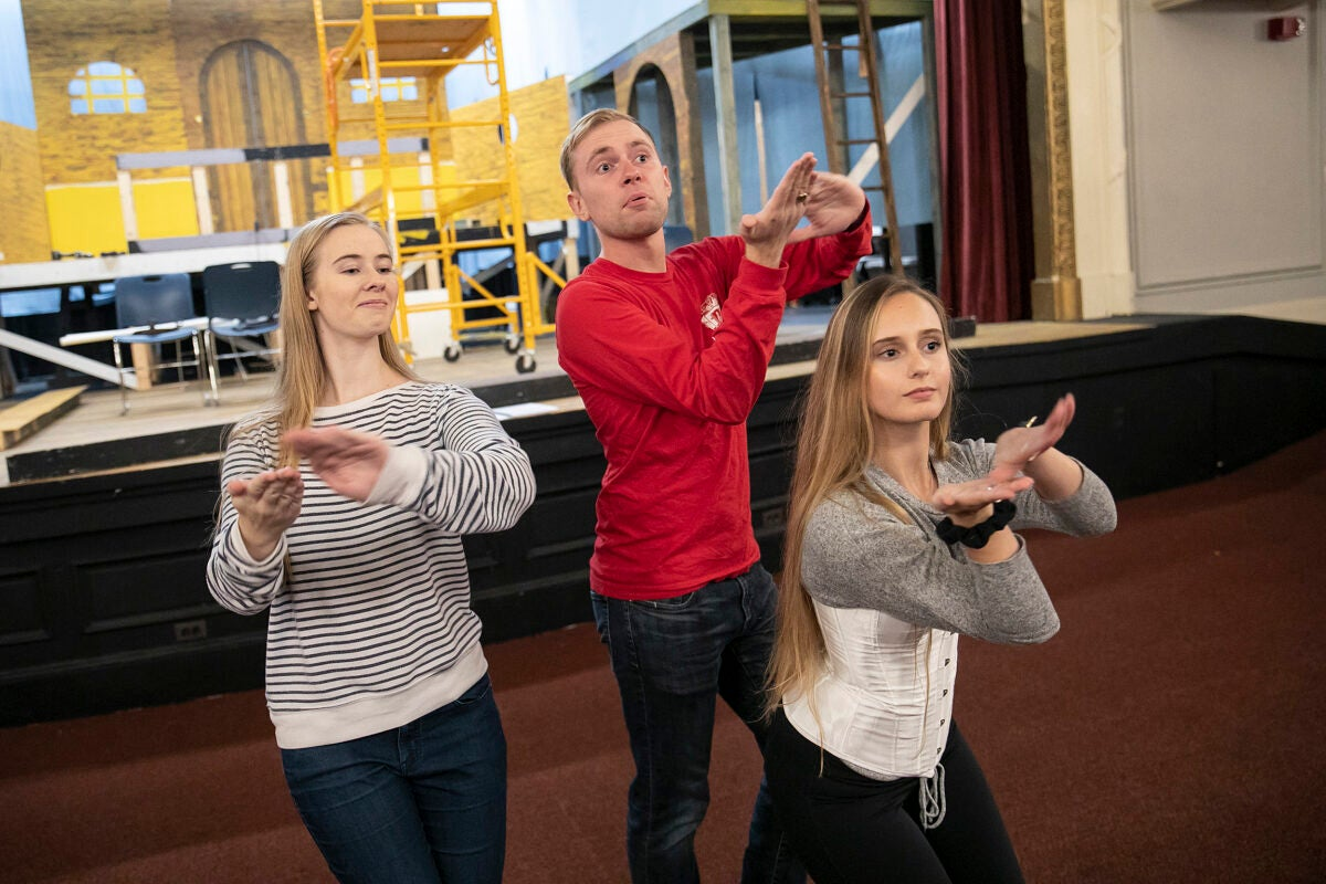 Three cast members pose during rehearsal