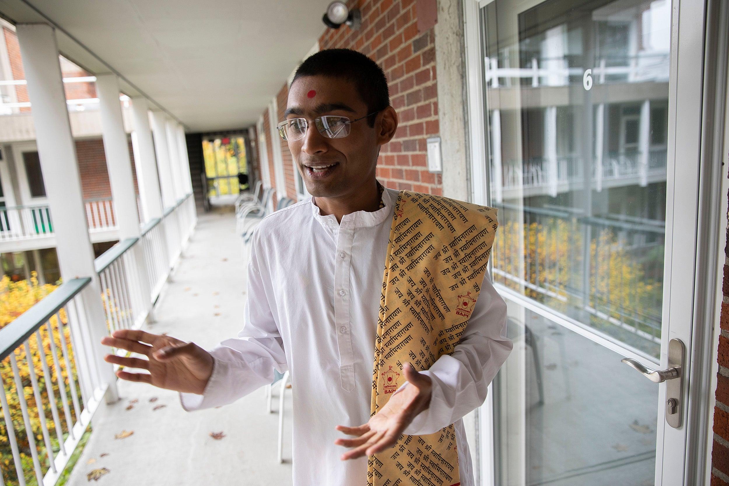 Sadhak Akshar Parsana talking in the walkway at the Divinity School.