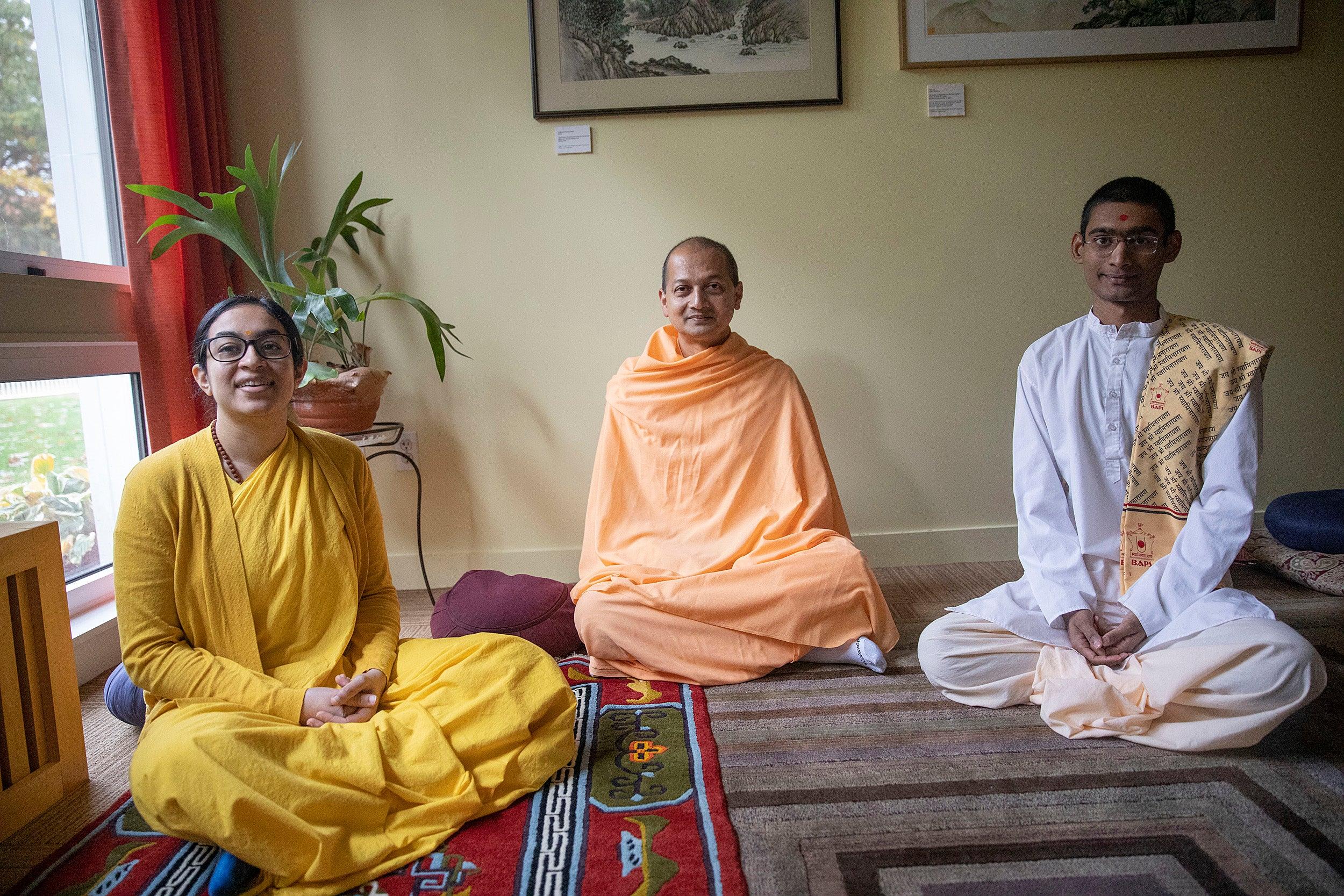 Three Hindu monastics at Harvard Divinity School, all seated.