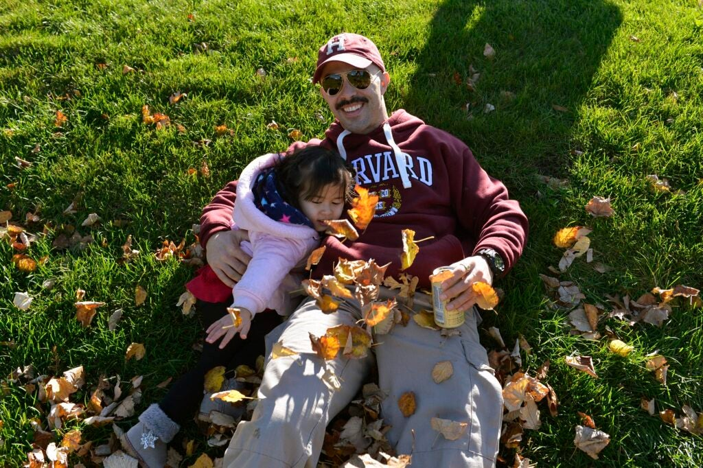 Nicholas Nesbit from Harvard Extension School rolls in the autumn leaves with his daughter Roisian, 2.