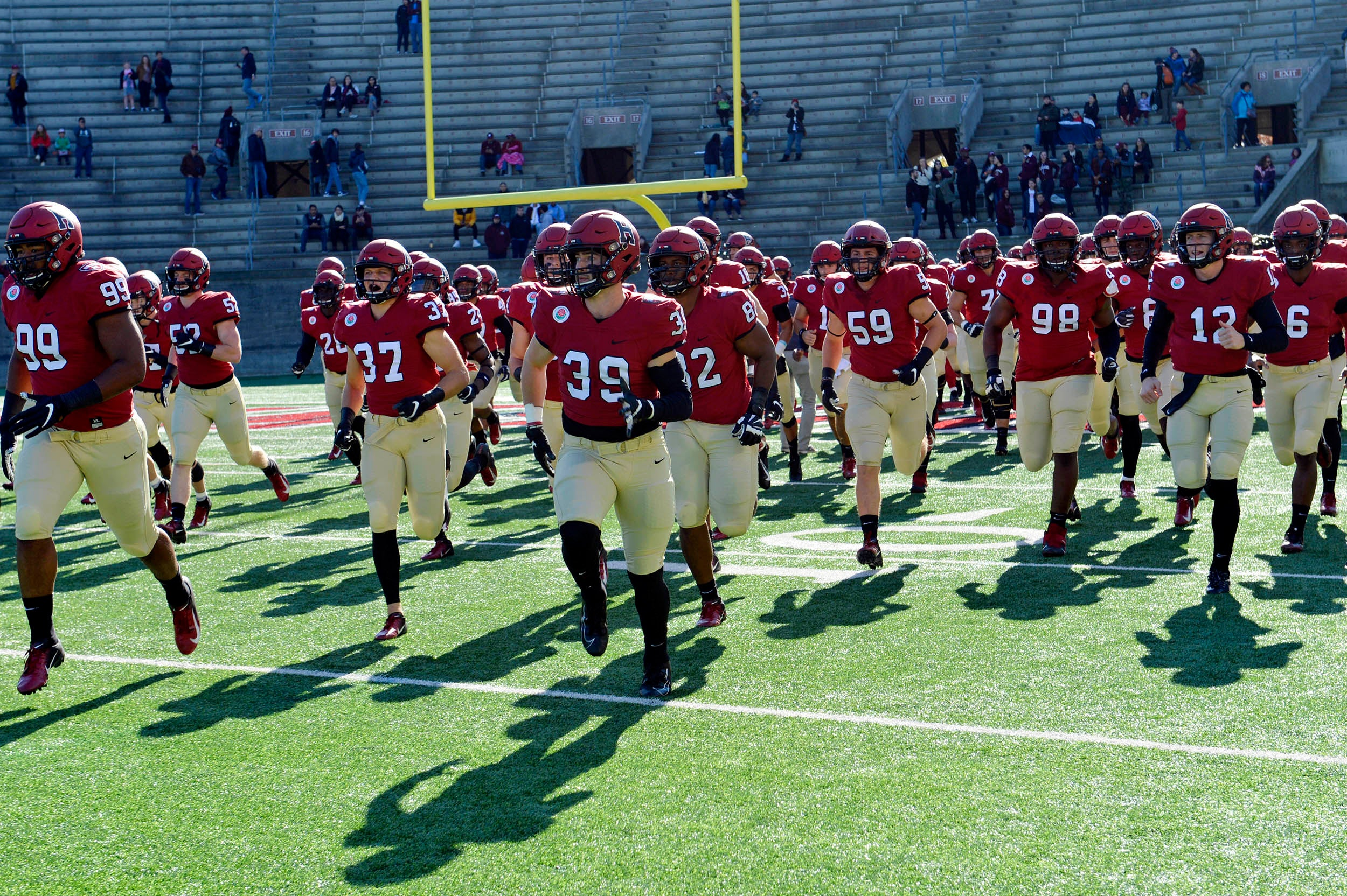 The Harvard football team takes the field against Dartmouth.