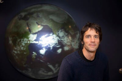 A portrait-style photo of professor in front of a large globe