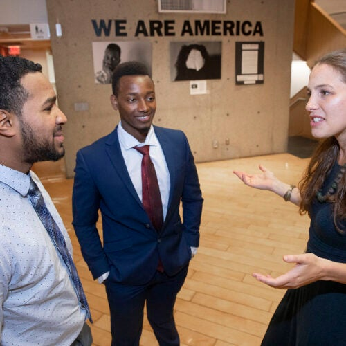 Teacher Jessica Lander with students Ezequiel Nunez and Robert Aliganyira in the 'We Are America' photo exhibit at Gutman Library.