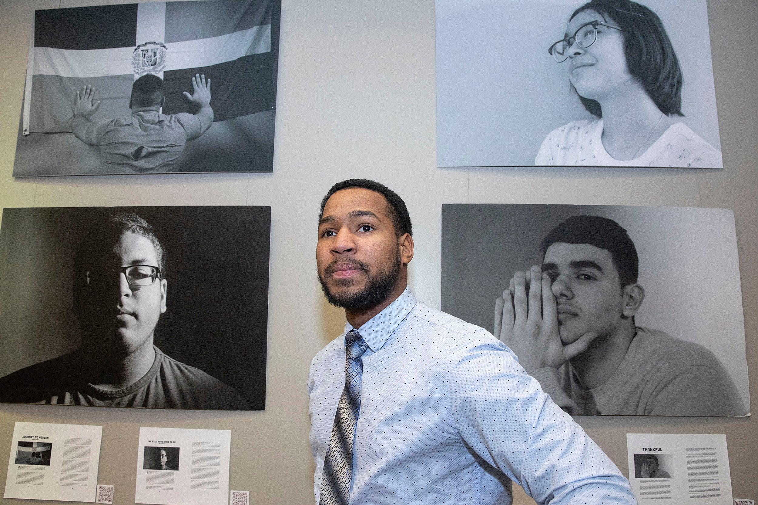 """Ezequiel Nunez with """"We Are America"""" portraits."""