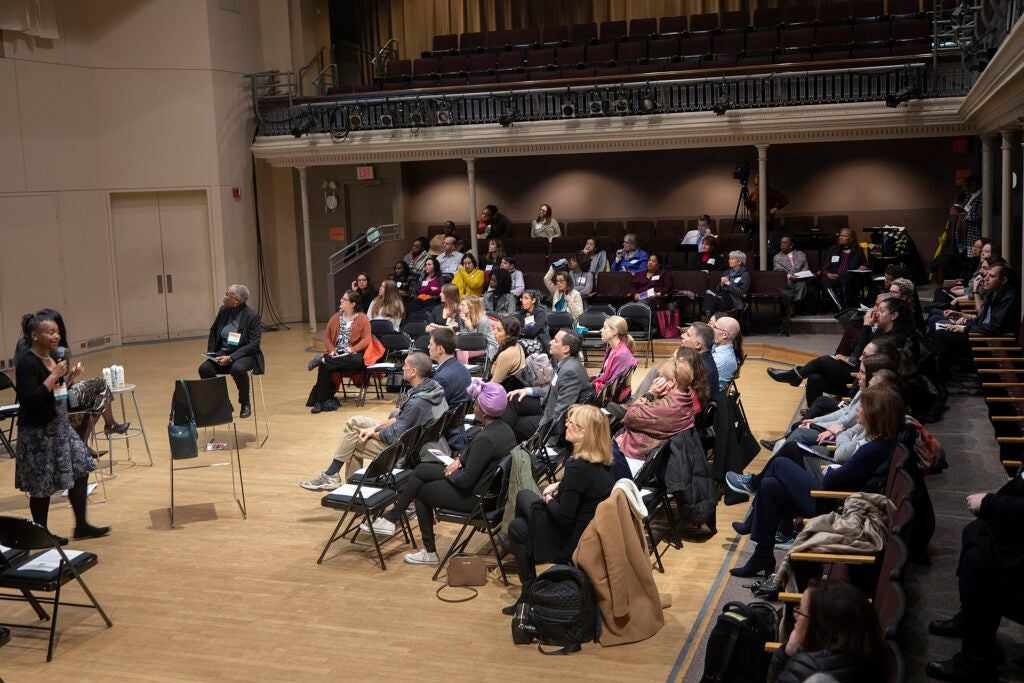 Audience in folding chairs listening to panelists.