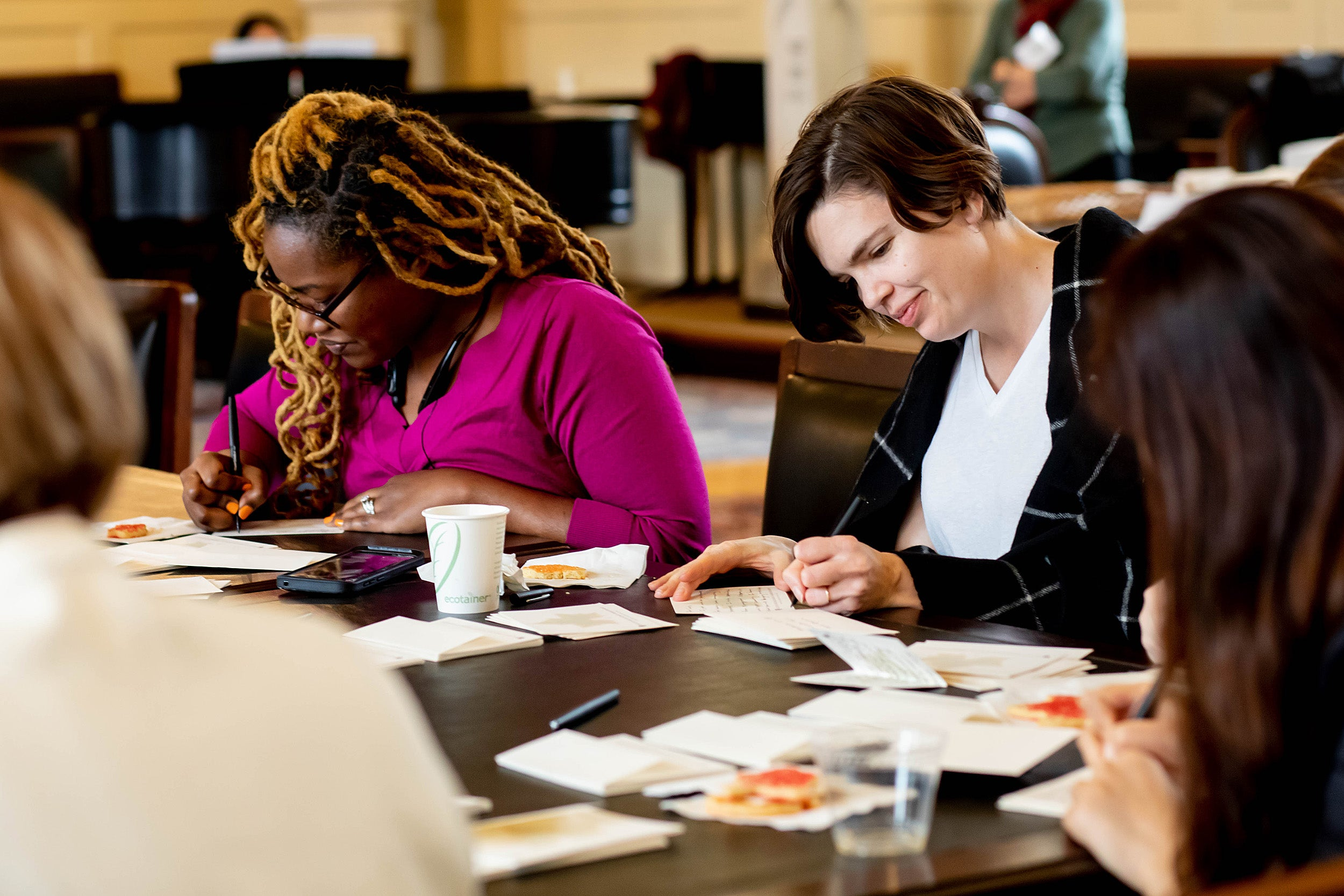 women writing thank-you notes at table.