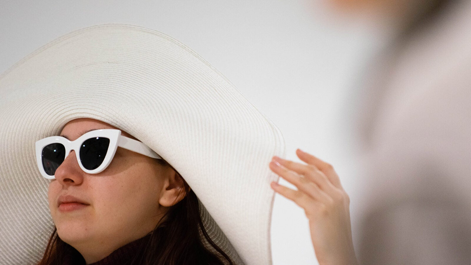 Allie Jeffay wears a large, white sun hat and sunglasses.
