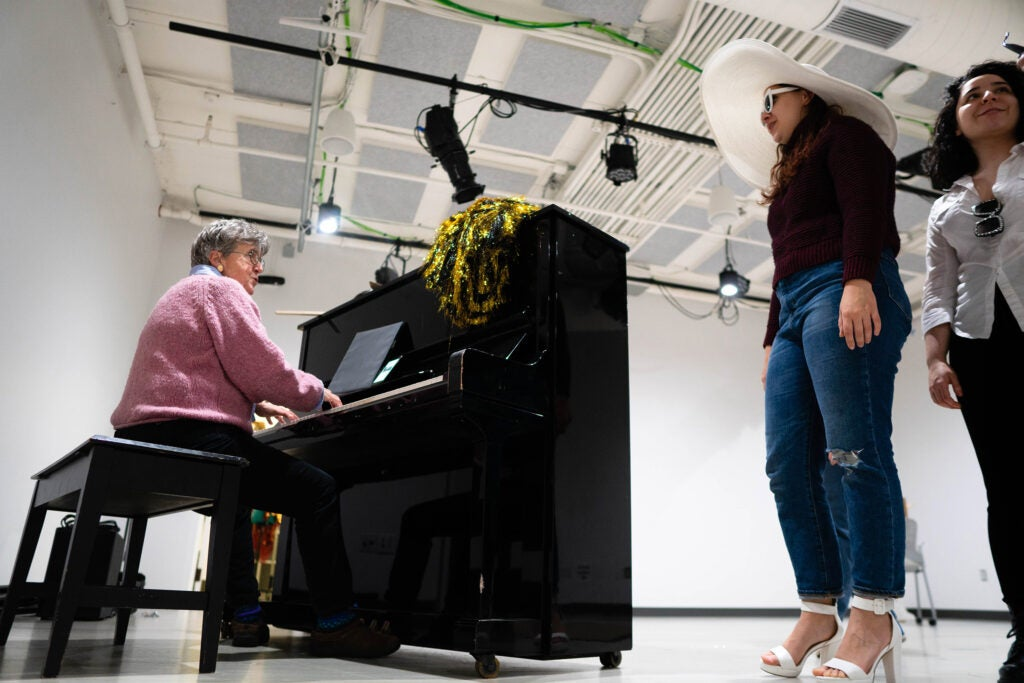 Musical director Catherine Stornetta plays piano and runs performers through vocal warm-ups before rehearsal.