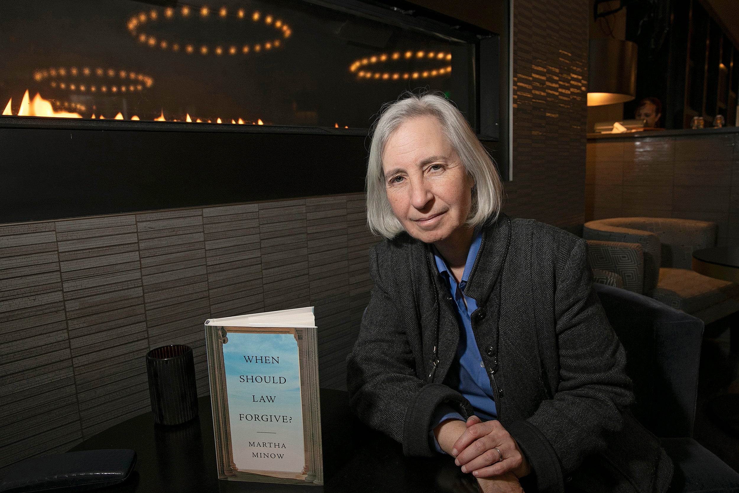 Professor Martha Minnow sitting at a table with her book in front of her.