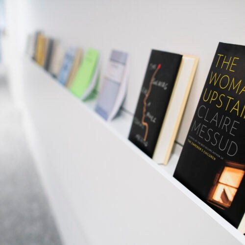 A row of books lines a shelf in the Department of English's creative writing program in Lamont Library.