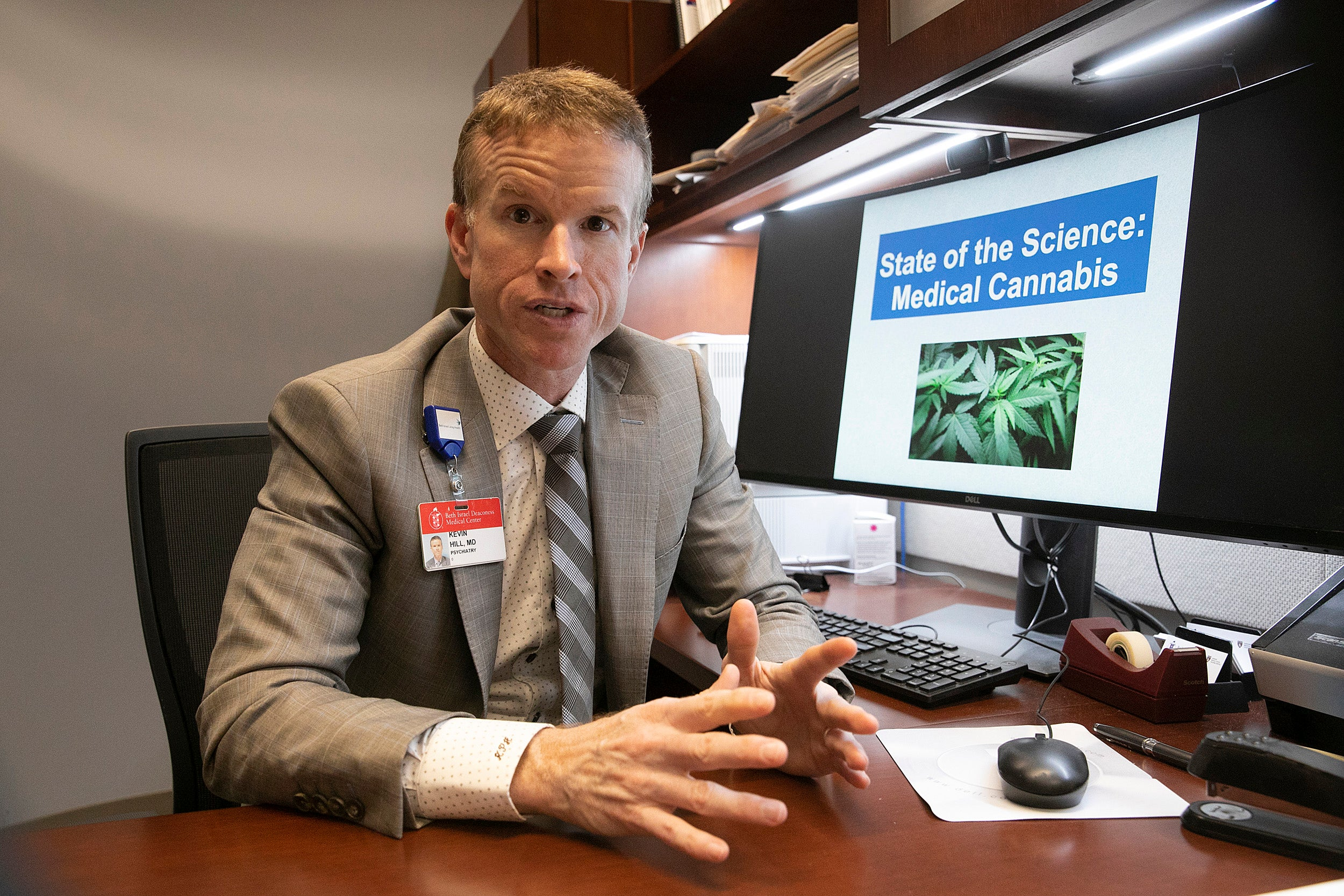 Professor sitting at desk with computer monitor showing marijuana.