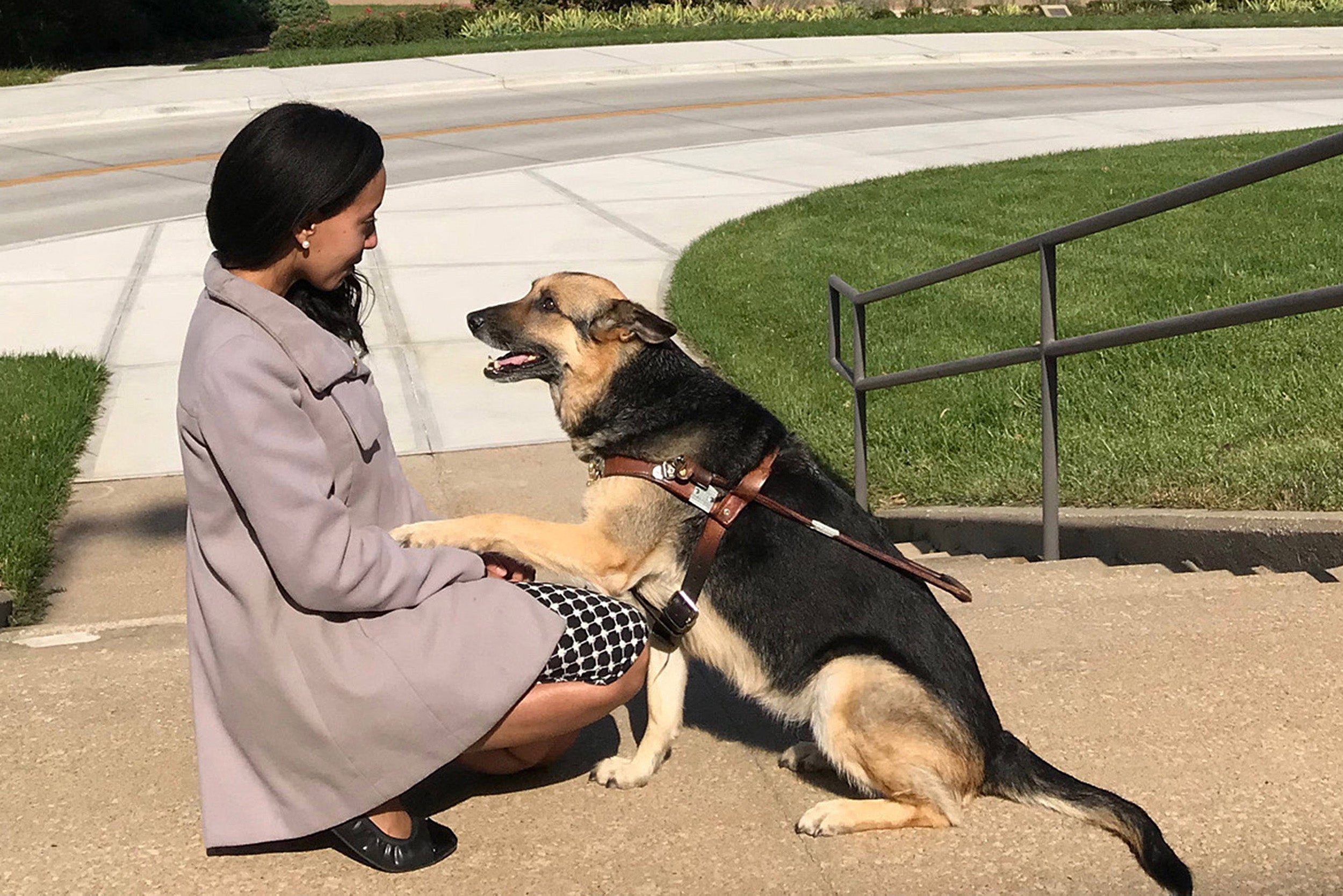 Haben Girma kneels with her dog, who has placed one paw on her knee