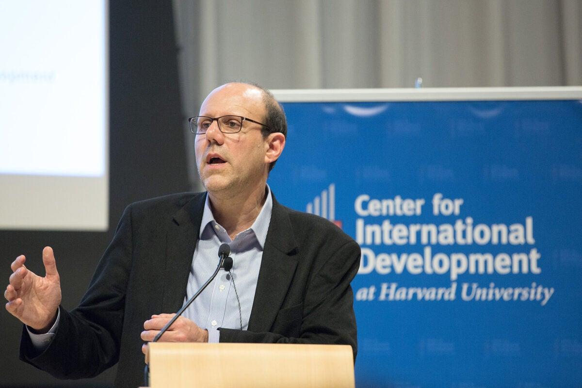 Michael Kremer speaking at a podium