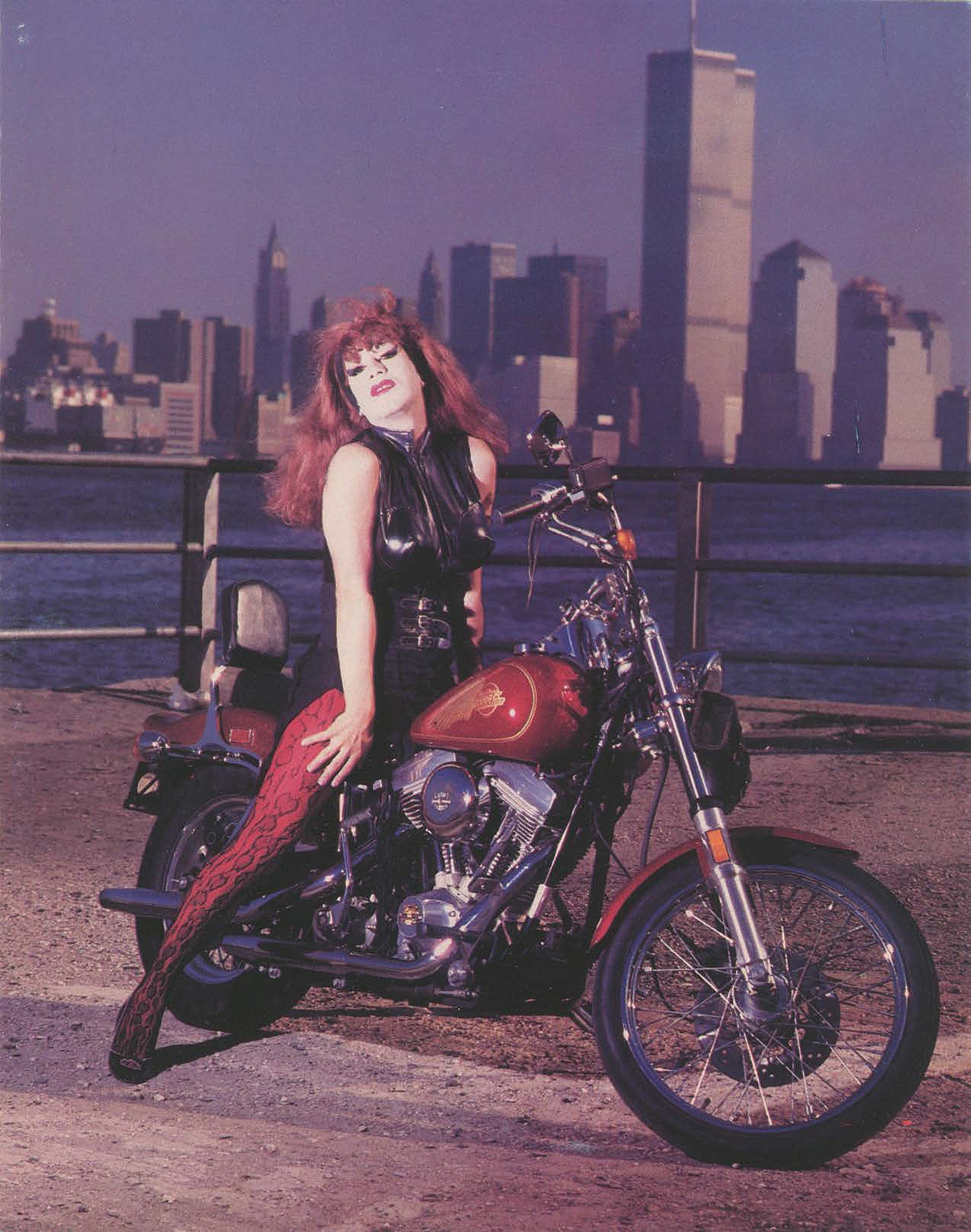 Joey Arias on motorcycle with New York City skyline in background.