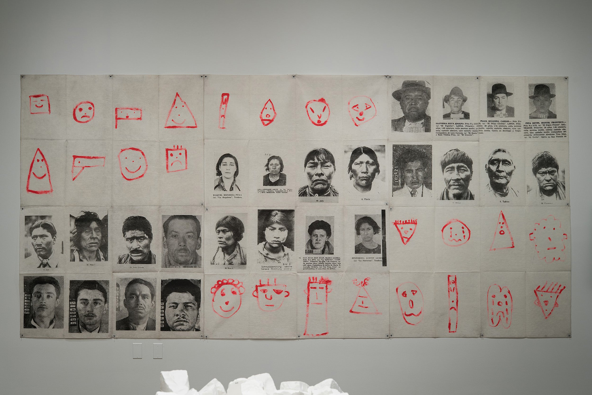 A large mural of photographs and children's drawings.
