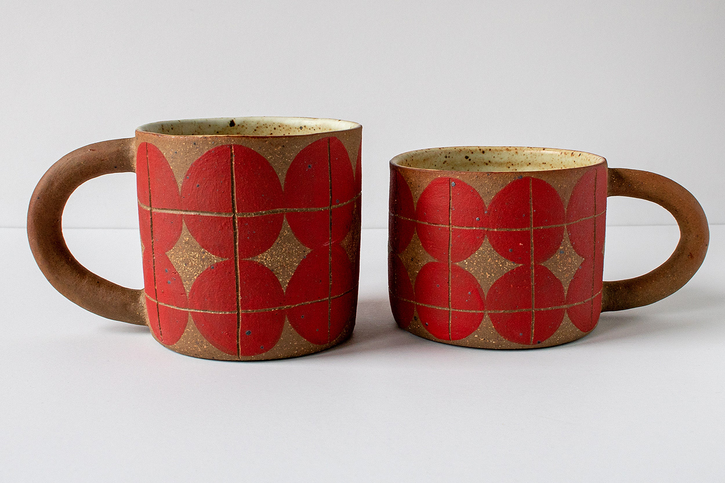 Two gold and red mugs by artist Alice Nasto.