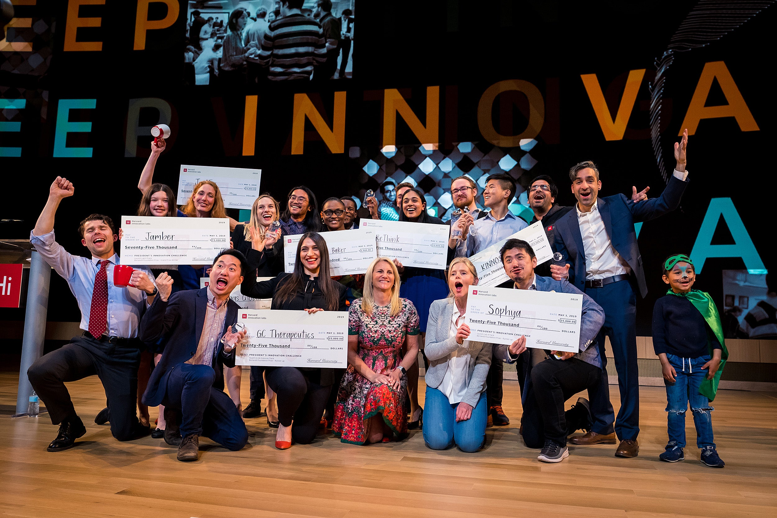 Innovation Challenge awardees celebrate onstage with their prize money checks.