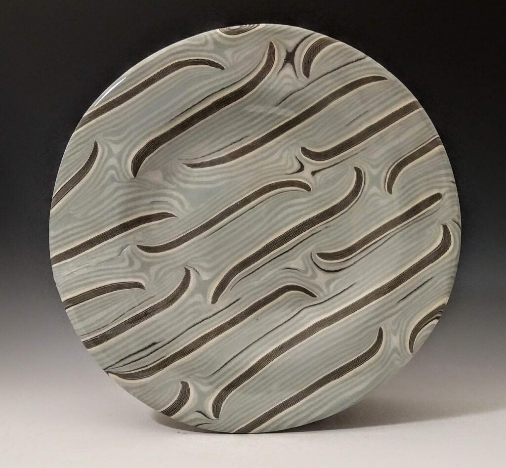 A decorative plate with swirls as decoration.