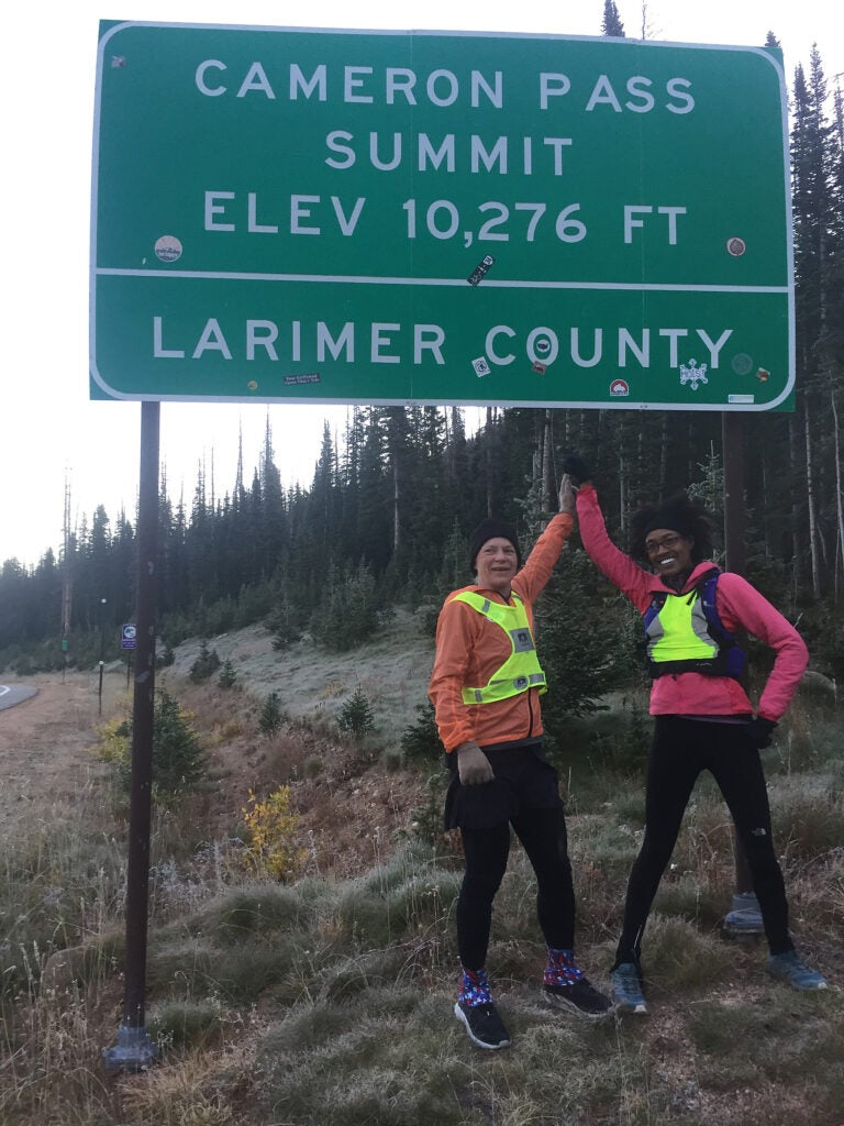 Two women hold hands triumphantly under landmark sign.