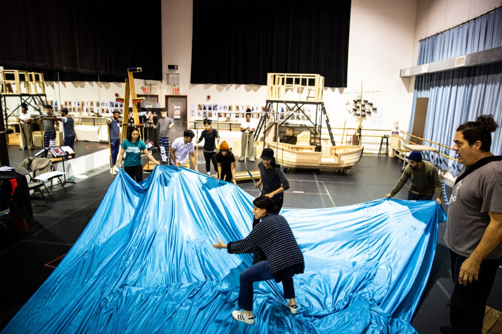 The cast rehearses in the studio, using a large blue sheet as the ocean.