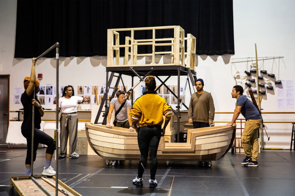Cast members stand around a wooden prop boat as a choreographer looks on in the center.