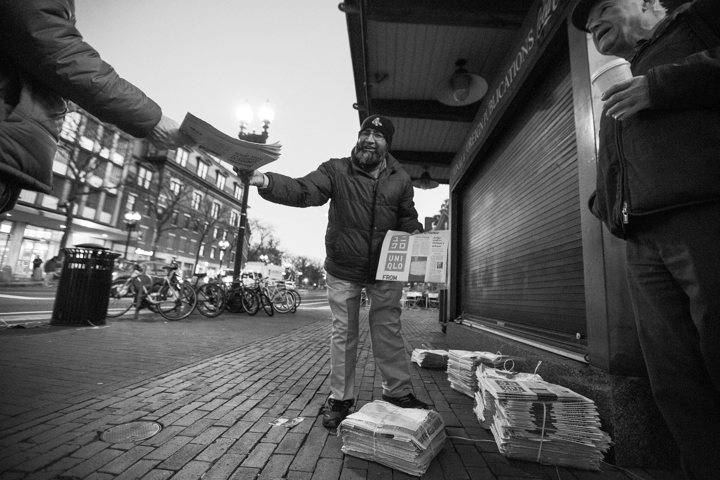 Mohamed Rahman hands out newspapers in Harvard Square.