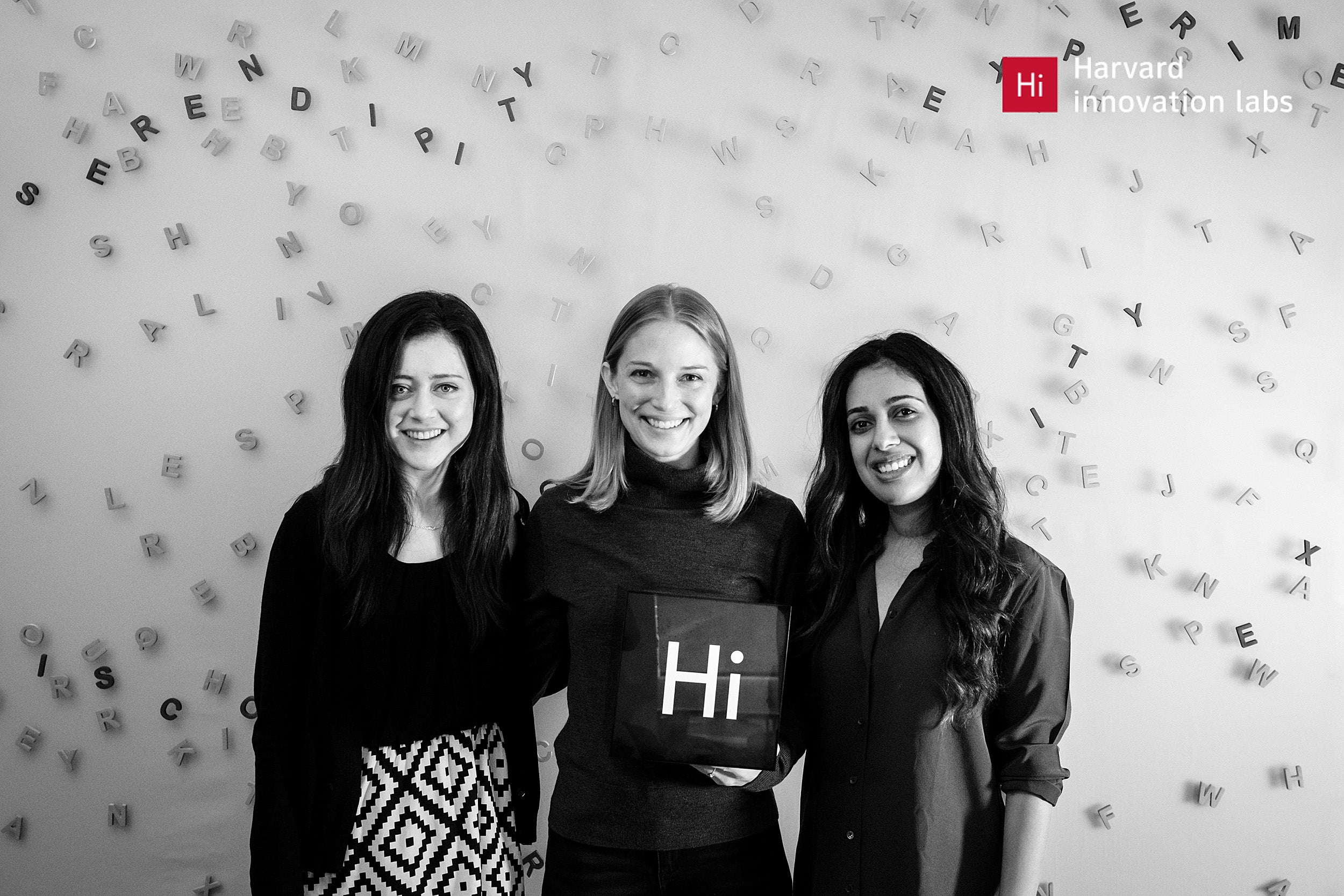 """Three women standing together holding a small sign that reads """"Hi"""""""