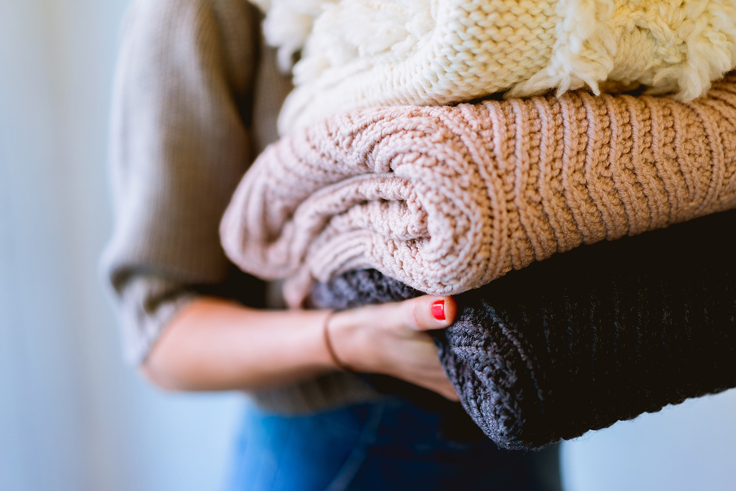 Close up of person's hands holding stack of folded sweaters.