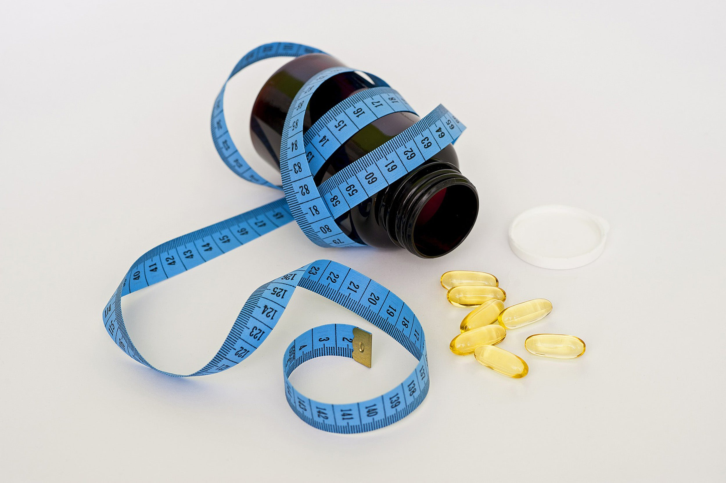 A blue measuring tape wrapped around a medicine bottle, with loose pills scattered around the open lid.