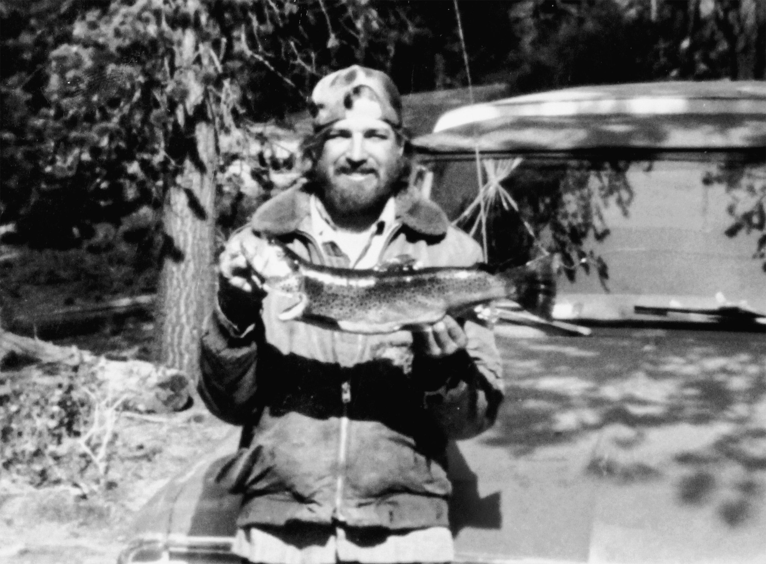 Bearded man holding large trout.