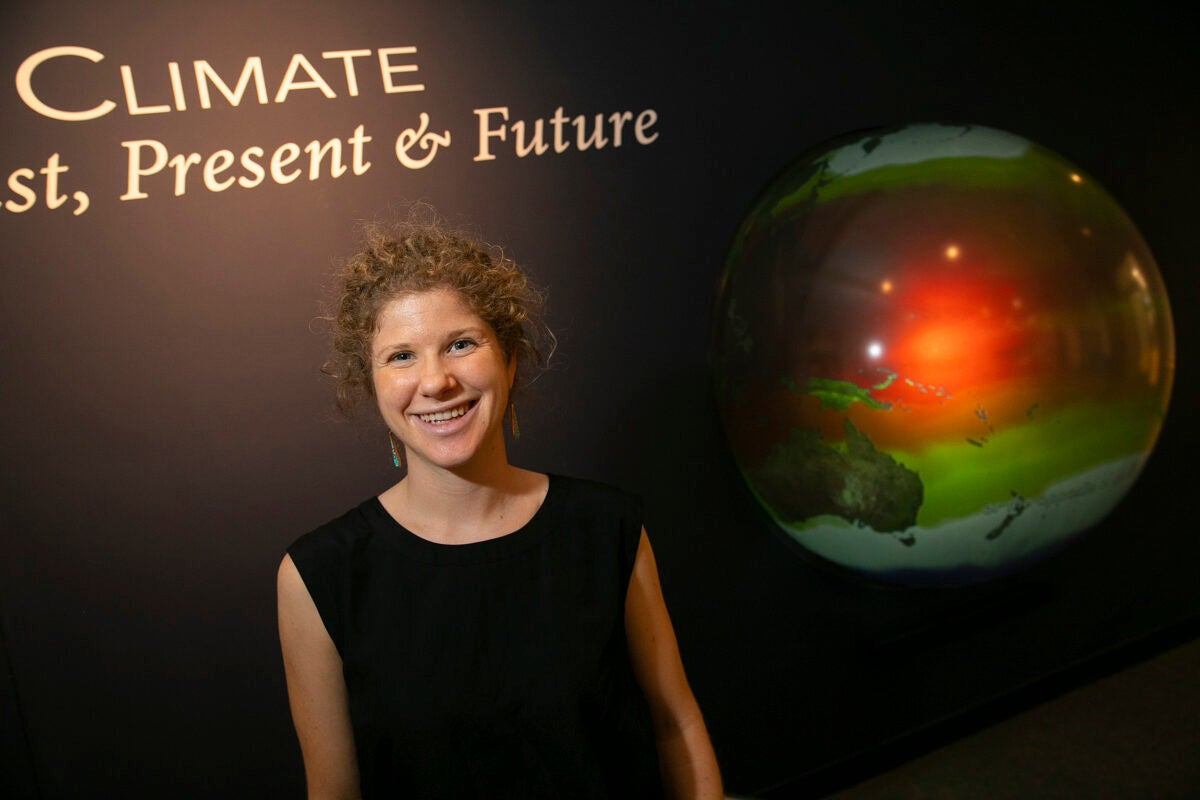 Tamara Pico in front of an image of the Earth.