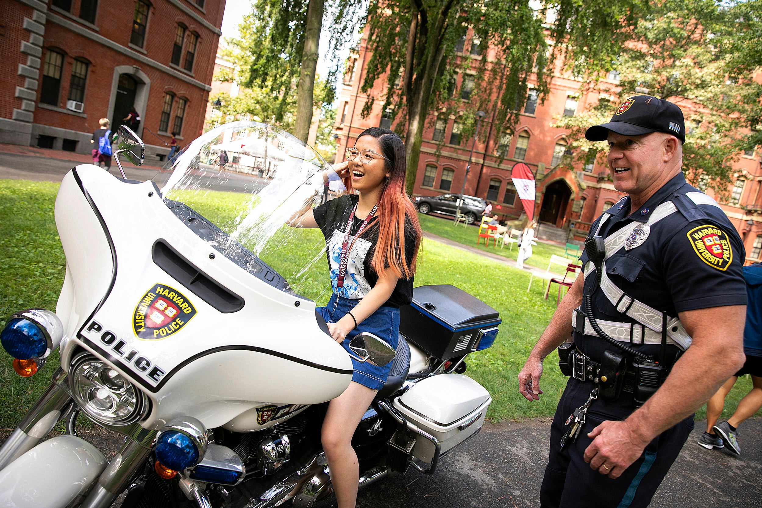 Student sits on police motorcycle, with the officer standing by.